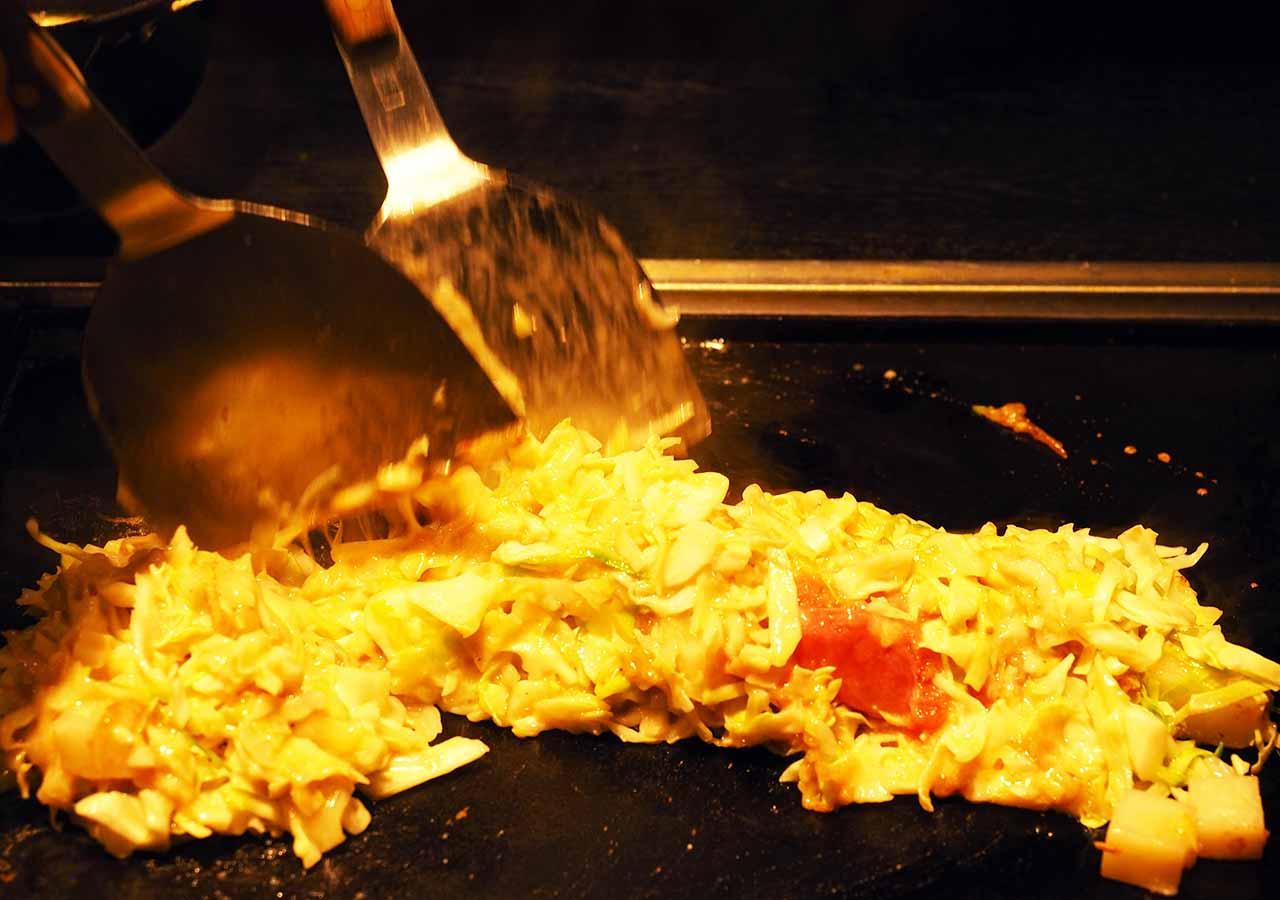 月島名物もんじゃ だるま 東京スカイツリータウン・ソラマチ店のもんじゃ焼き調理
