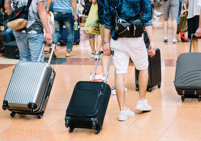 空港でスーツケースを持って移動する人々