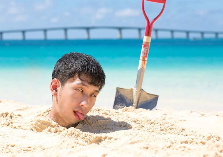 ビーチの砂浜に埋められた男性