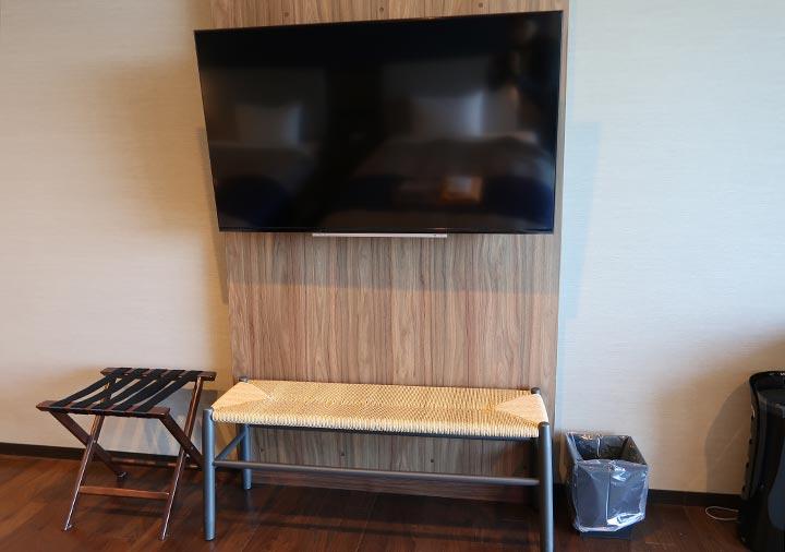 レックスホテル別府 客室のTV、スーツケースラック、ベンチ